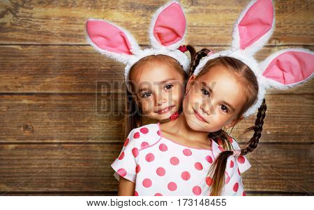 Happy easter! cute twins girls sisters dressed as rabbits on wooden background