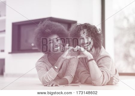 beautiful young multiethnic couple used tablet computer on the floor of their luxury home in front of fireplace autumn day