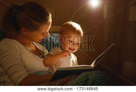 mother reads to baby the book before going to sleep in bed