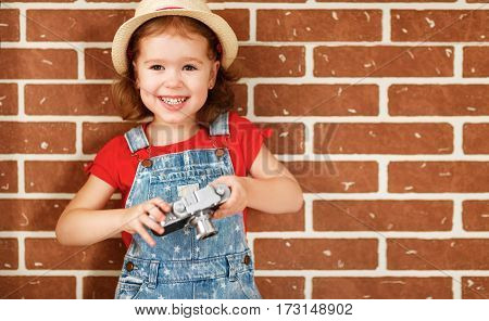Happy child girl photographer with a camera at the brick wall