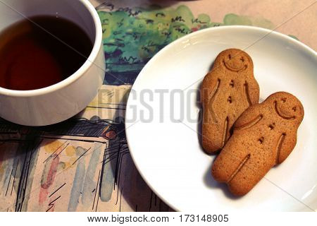 Black tea and gingerbread men cookies in a white bowl in a cafe