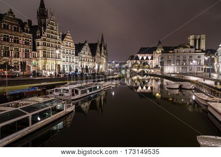 GHENT BELGIUM - 18TH FEB 2016: A view towards Sint-Michielskerk (Saint Michael's Church Ghent) in Ghent at night from the Graslei and Korenlei. Boats and other buildings can be seen.