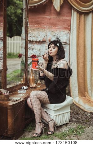 retro girl sitting at a dressing table, holding a candle and smoking cigarette with mouthpiece