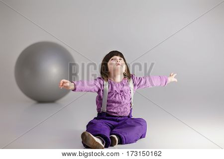 little cute girl in purple clothes with arms outstretched and with a large ball for fitness on gray background.