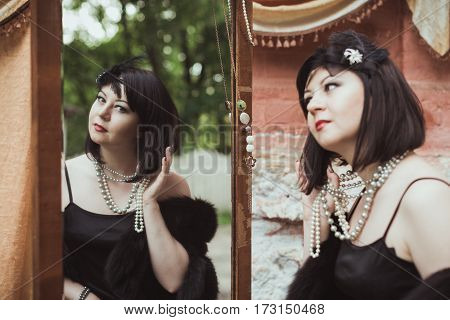 Portrait of a woman in retro style, looking in the mirror and holding a flower