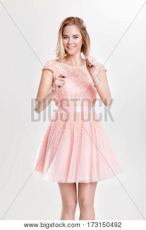 beautiful blond sensual woman in a pale pink cocktail dress dancing and having fun on grey background