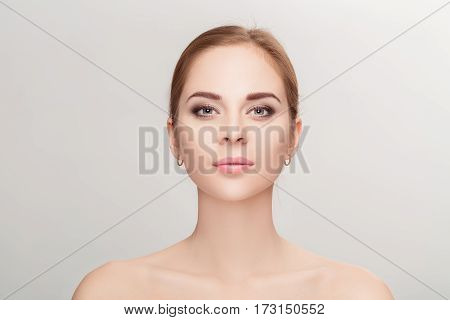 Front portrait of beautiful young blonde woman with green eyes on grey background closeup. girl with clean skin