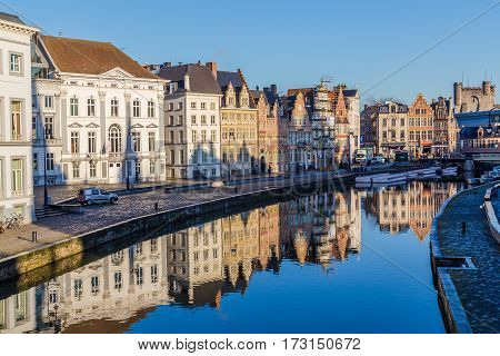 GHENT BELGIUM - 19TH FEB 2016: A view of beautiful old buildings along Korenlei and the River Leie in Ghent Old Town during the day. Reflections can be seen in the water.
