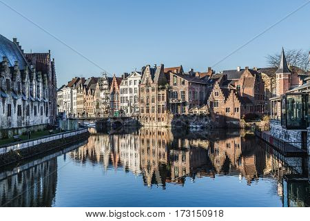 GHENT BELGIUM - 19TH FEB 2016: A view along the River Leie in central Ghent during the day. Old buildings and reflections can be seen.