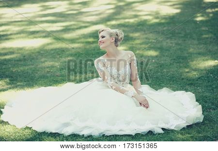 Happy pretty girl or cute bride with beautiful makeup and blond hair hairstyle in white sexy wedding dress smiling and sitting on green grass on sunny summer day outdoors on natural background