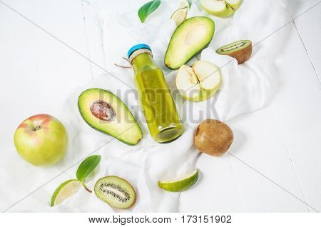 Green smoothie in bottl with avocado apple and kiwi on white wooden background. Top view