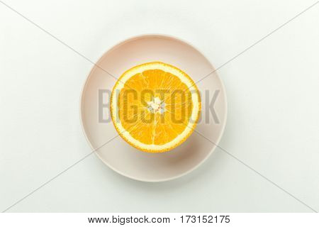 Half of fresh cut orange fruit on a plate on white background, top view with copy space. Healthy natural food concept