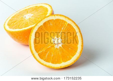 Two halves of fresh orange fruit in a cut on white background, macro close up photo. Healthy and natural food concept. Not isolated