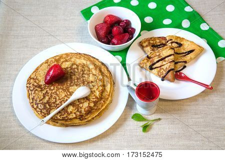 Beautiful baked pancakes with red berries and chocolate on a white plate. On the table green with white polka dots linen towel white red Cup and a red spoon.