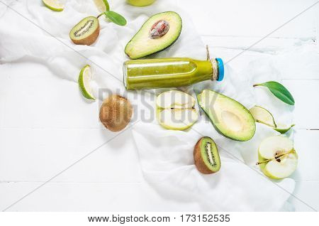 Green smoothie in bottl with avocado apple and kiwi on white wooden background.