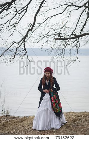 Beautiful boho-style girl with dreadlocks in a white wedding dress on background of a lake and pine forest soft focus faded colors