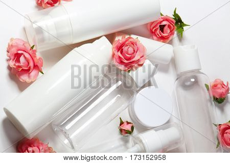 White cosmetic bottles on white background. Wellness spa and body care bottles collection with spring parfume flowers. Beauty treatment bathroom set.