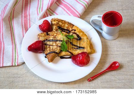 Beautiful baked pancakes with red berries and chocolate on a white plate. On the table linen towel with stripes and white Cup with red spoon.