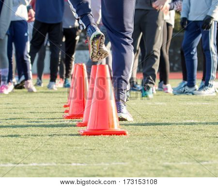 A runner does a dead leg drill over orange cones on a green turf field while his teammates watch