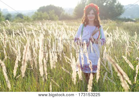 Pretty smiling girl in a garland of poppy flowers and national embroidered ethnic dress posing in the meadow of yellow field flowers lit with summer sun