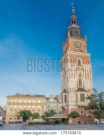 KRAKOW POLAND - 15TH OCTOBER 2016: Old Town Hall Tower and Rynek Glowny in Krakow in the morning. People can be seen.