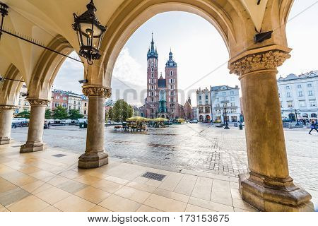 KRAKOW POLAND - 15TH OCTOBER 2016: St. Mary's Basilica shops and buildings on Rynek Glowny (Main Square) in Krakow in the morning.