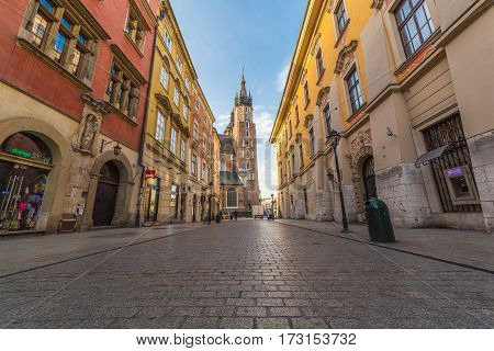 KRAKOW POLAND - 15TH OCTOBER 2016: Colourful architecture along Florianska street with St. Mary's Basilica in the distance in Krakow. People can be seen.