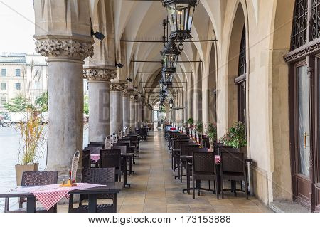 KRAKOW POLAND - 15TH OCTOBER 2016: Restaurants along the side of the Cloth Hall in Rynek Glowny. Lots of tables can be seen.