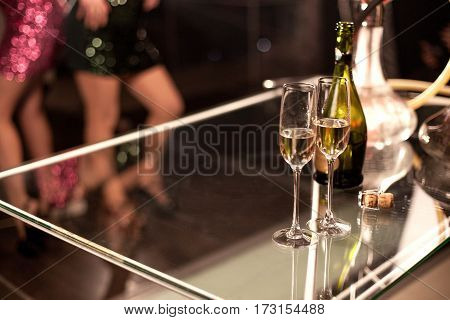 Two glasses of wine or champagne placed on a glass table in a bar or a restaurant