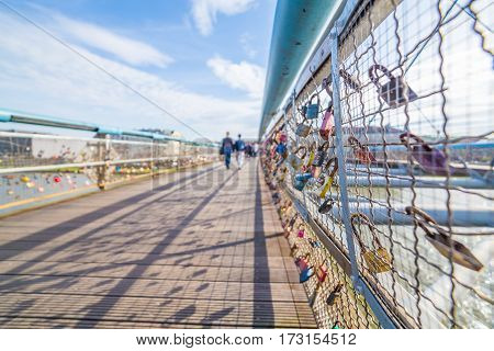 KRAKOW POLAND - 15TH OCTOBER 2016: Kladka Ojca Bernatka Bridge in Krakow seen with padlocks attached to it which is normally a sign of love. People can be seen in the distance.