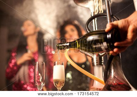 Wine pouring into a glass. Two women smoking hookah on a background.