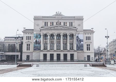 RIGA LATVIA - 2ND JAN 2017: The outside of the Latvian National Opera during the day in the winter. Snow and people can be seen.