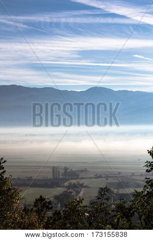 Idyllic morning scene of valley in fog mist with mountain between land and bright sky covered in sunlight as beautiful season background