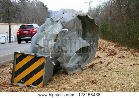 Cars travel by a curled, wrecked, mangled guardrail