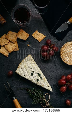 Overhead view of Cheese, Crackers, Grapes and Glasses of Red Wine for Dinner Party