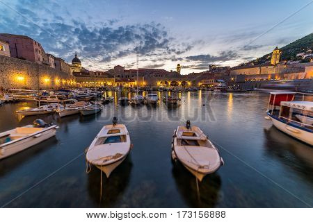 DUBROVNIK CROATIA - 11TH AUGUST 2016: Boats docked in the Dubrovnik Old Port at dusk.