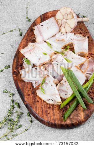 tasty bacon with spices on wooden cutting board on a gray background. flat lay. copy space. close up.