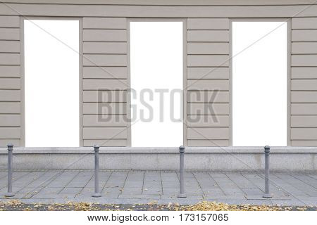 Three blank vertical mockups on a building wall. Autumn street. Front view