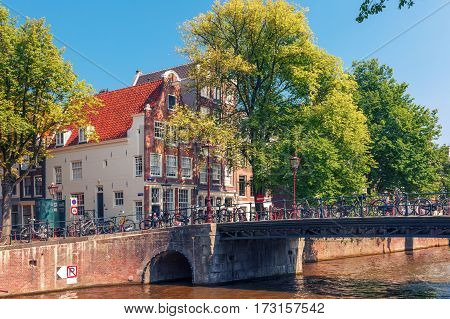Amsterdam canal, bridge and typical houses in the sunny summer day, Holland, Netherlands.