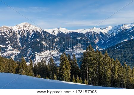 Tree runs at a ski resort in the winter. Fresh snow mountains and piste can be seen.