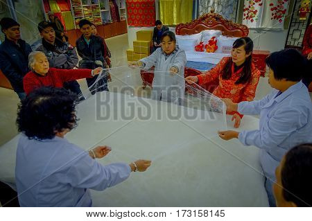 BEIJING, CHINA - 29 JANUARY, 2017: Visiting traditional chinese silk factory, workers performing their tasks creating the smooth textile.