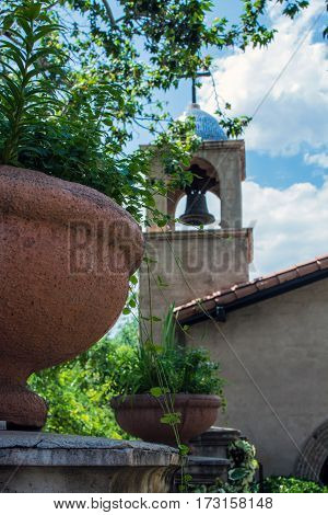 Terra cotta pots on a wall wth a chapel steeple in the background
