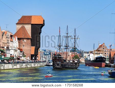 GDANSK POLAND - AUGUST 27 2016: Old city with medieval wooden port crane the oldest in Europe Motlava river tourist pirate ship boats kayaks and crowd of people walking along the quay