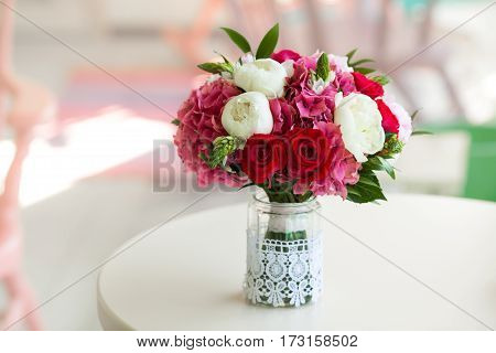 Beautiful wedding bouquet with roses and peonies in glass vase on white round table close up.