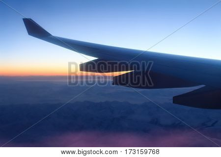 Wing aircraft in contre against the background of orange sunset.