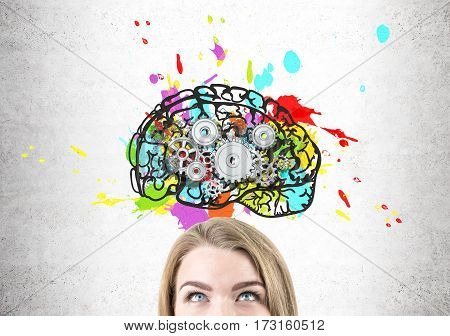 Close up of a blond woman head with gray eyes. She is standing near a concrete wall with a colorful and bright brain drawing with cogs inside it.