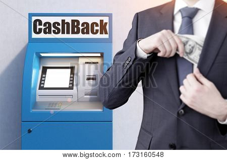 Close up of a businessman wearing a black suit who has taken money from a blue atm machine. He is puting it in the pocket.