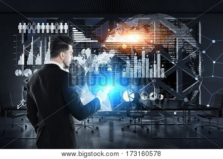 Rear view of a businessman wearing a suit and holding his smartphone while standing near a glassboard with graphs and a world map drawn on it. Toned image.