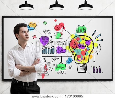 Portrait of a confident brown haired businessman standing with crossed arms near a whiteboard with a colorful and bright idea sketch.
