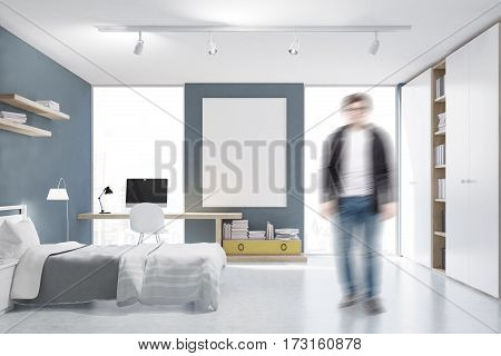 Man In A Gray Walled Bedroom With Study Corner
